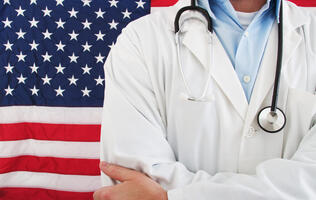 Doctor Standing in Front of American Flag