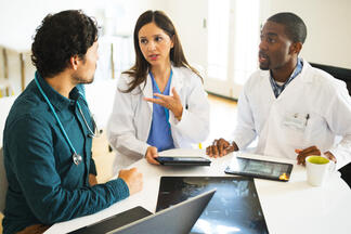 Image of three doctors in a meeting that looks like they are settling on a decision
